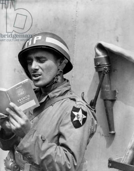 U.S. Army MP (Military Police) practices French on a ship taking him to Normandy. June 15, 1944. World War 2