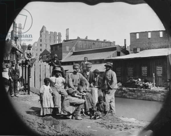 A newly freed African American group of men and a few children posing by a canal against the ruins of Richmond, Virginia. Photo made after Richmond was taken by Union troops on April 3, 1865