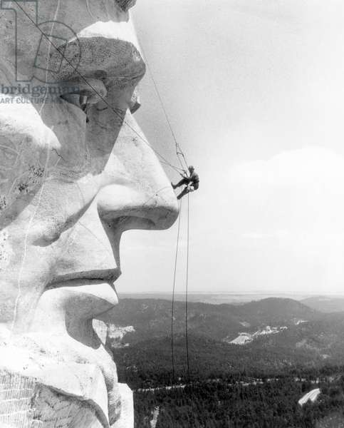 A maintenance worker on the nose of Mount Rushmore's Abraham Lincoln, South Dakota, c. 1960s.