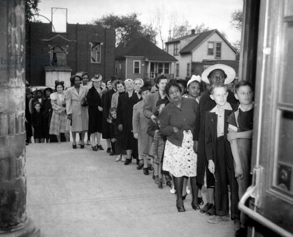 Racially integrated waiting line in a Northern American city during World War 2. They are waiting to purchase rationed sugar, c. 1942-45