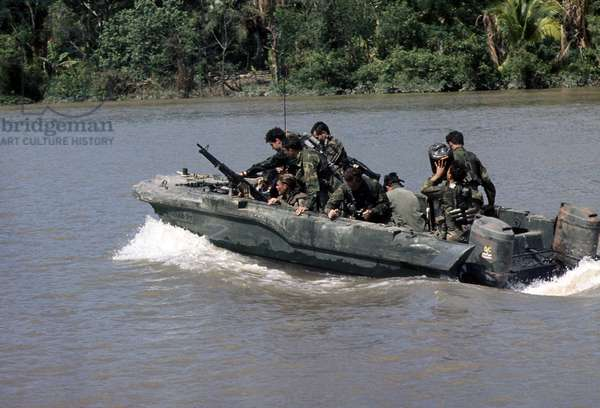 Vietnam War, Republic of Vietnam, members of U.S. Navy Seal Team One move down the Bassac River in a Seal team Assault Boat (STAB) during operations along the river south of Saigon, c.1960s