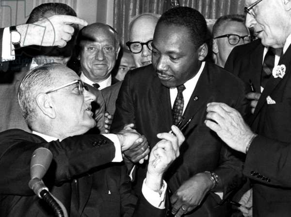 front row: President Lyndon Johnson handing a pen to Martin Luther King Jr., during the ceremonies for the signing of the Civil Rights bill at the White House, Washington D.C., July 2 1964.