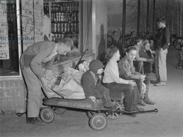 Youngsters hiring out their express wagons to haul groceries in suburban Greenbelt, Maryland. World War 2 tire and gasoline rationing created this business opportunity. Nov. 1942