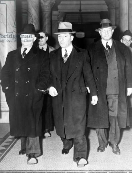 Louis 'Lepke' Buchalter, center, handcuffed to J. Edgar Hoover (left), at entrance to courthouse in New York City in 1939-40. With a ,000 reward on his head, he was tricked into surrendering to Hoover by a 'friend,' Moey Dimples. Buchalter was executed on March 4, 1944