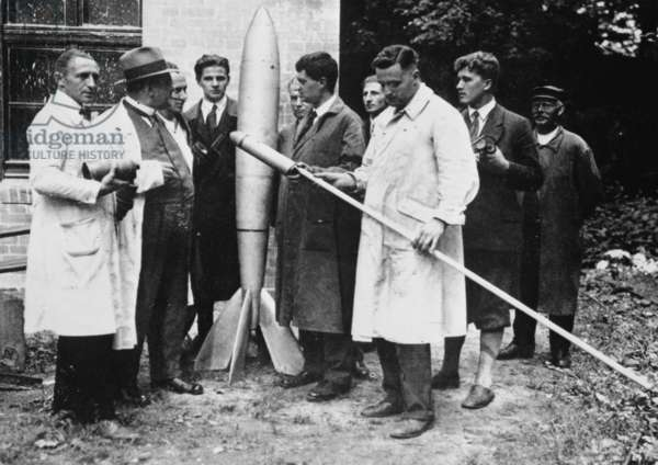 Klaus Riedel holding an early version of the Minimum Rocket 'Mirak'. Rudolph Nebel (left), Franz Ritter (second from left), Kurt Heinisch (left of rocket), Hermann Oberth (fifth from right), Klaus Riedel (front, in white), Wernher Von Braun (second from right), 1930. ©Nasa/Courtesy Everett Collection