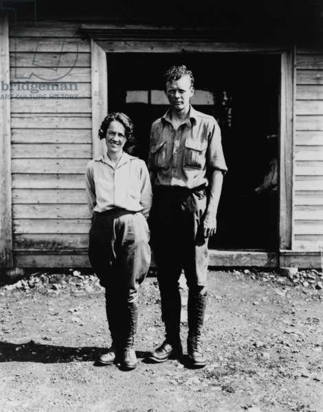 Charles and Anne Morrow Lindbergh, standing in front of cabin on Etarofu Island, Russia in 1935. After the conviction of Hauptman for the kidnapping of their first child, the Lindberghs continued flying and moved their growing family to Europe for several years