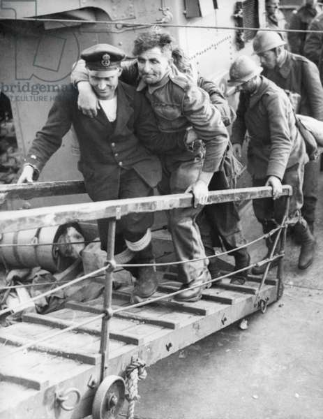 A British sailor assisting a wounded Tommy followed by French Troops. They are arriving safely in England from the beaches of Dunkirk. World War 2. May 26-June 4, 1940