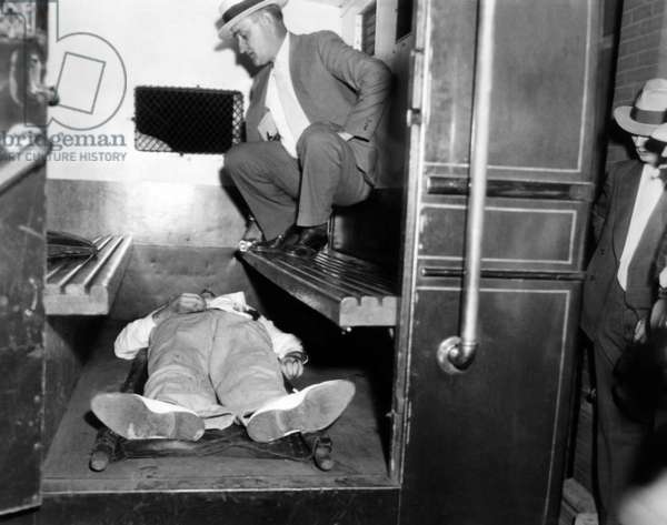 John Dillinger, dead with toes up in a police patrol wagon, is taken from the scene of his killing by FBI agents in Chicago. July 22, 1934
