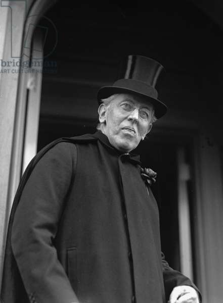 Ex-President Woodrow Wilson (1856-1924), weakened by a severe stroke in 1919, stands in the doorway of his home on his 65th birthday, Dec. 28, 1921