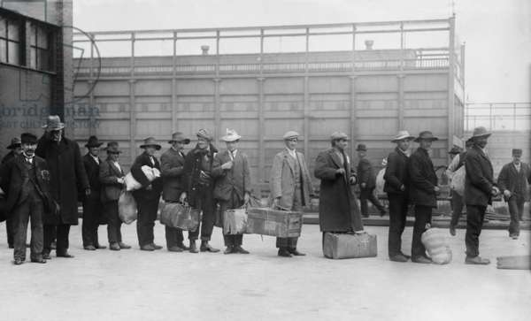 Italian men await admission processing at Ellis island, were among the 2,000 Italian immigrants the arrived on the Prinzess Irene which grounded on Fire Island sandbars. c. 1910