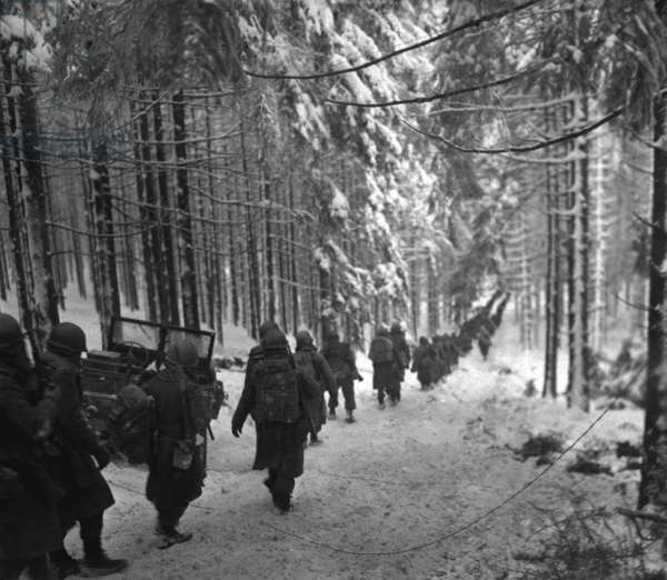 U.S. soldiers march along the snow-covered road in the Battle of the Bulge. They were advancing to block retreating German army by cutting off the St. Vith-Houffalize road in Belgium. January 24, 1945. World War 2