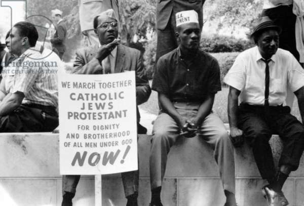 "Civil Rights, the civil rights march from Selma to Montgomery, Alabama in 1965. Photograph shows some participants in the civil rights march sitting on a wall resting, one holds a placard which reads, ""We march together, Catholics, Jews, Protestant, for dignity and brotherhood of all men under God, Now!"""
