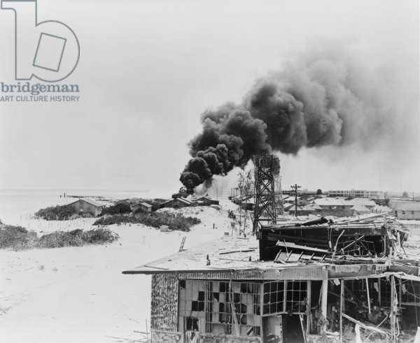 Smoke rising from burning oil tanks on Sand Island, Midway, after Japanese air attack, June 4, 1942. This marked the beginning to the two day Battle of Midway, which resulted in a decisive U.S. victory and the withdrawal of Japanese forces. World War 2