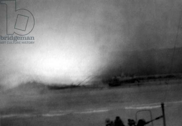 Large explosion near U.S. landing craft and soldiers assaulting Omaha Beach on D-Day. Photograph taken from a ship approaching Omaha Beach during the Allied invasion of Normandy on June 6, 1944. World War 2