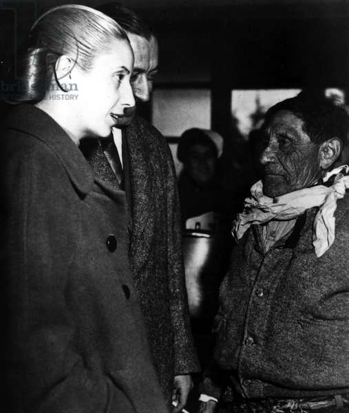 Eva Peron and President Juan Peron speak to a worker, late 1940s