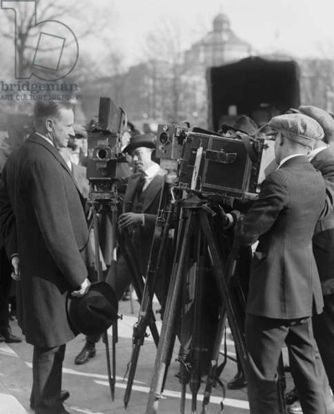 President Calvin Coolidge stands in front of newsreel cameras. 1921 in Washington, D.C