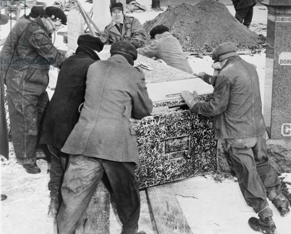 Burying Al Capone. Workmen at Mt. Olivet Cemetery in Chicago moving the vault with Al Capone's body. Feb. 6, 1947