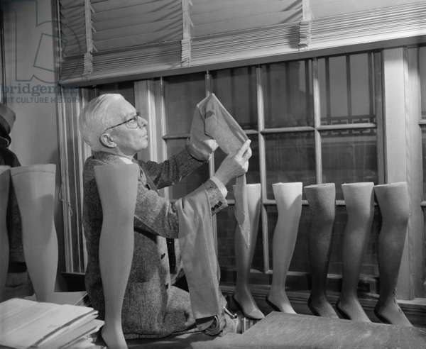 Agriculture Department fabric technician examines the cotton stockings that would replace those made by Japanese silk, after FDR froze all Japanese credits in the United States in response to the Japanese occupation of French Indo-China. The stocking industry had only two months supply of silk and nylon production was in it's infancy. July 1941