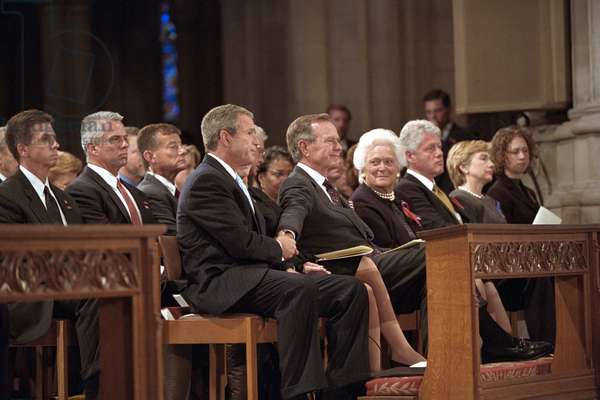 President George W. Bush grasps the hand of his father, former President George H. W. Bush. They were attending the National Day of Prayer and Remembrance service for the victims of the 9-11 Terrorist Attacks. Also in the front pew are, left from Bush 41, Mrs. Barbara Bush, Former President Bill Clinton, Sen. Hillary Rodham Clinton, and Chelsea Clinton. Sept 14, 2001