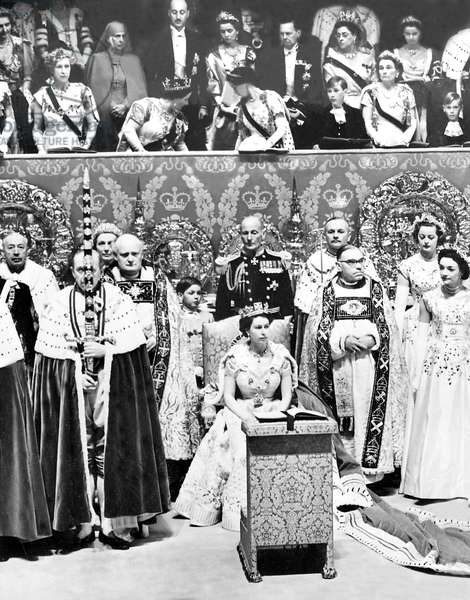 QUEEN ELIZABETH II, seated in the Chair of State in front of royal box where the Queen Mother (left) and Princess Margaret (right) try to get Prince Charles to stand for the coronation of his mother, June 2, 1953