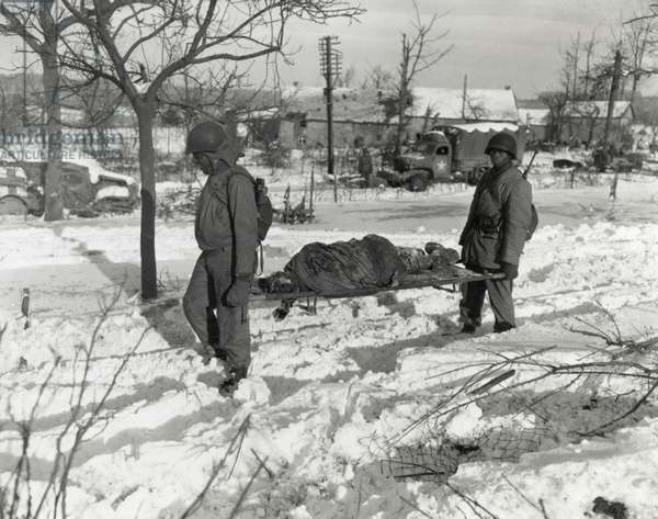 Two African American soldiers carry the body of an soldier on a stretcher during World War 2. Dead soldier is one of the victims of the German Waffen-SS massacre of 80 American POWs in Belgium, during the Battle of the Bulge, Dec. 1944. African Americans non-combat service battalions were often assigned mortuary tasks