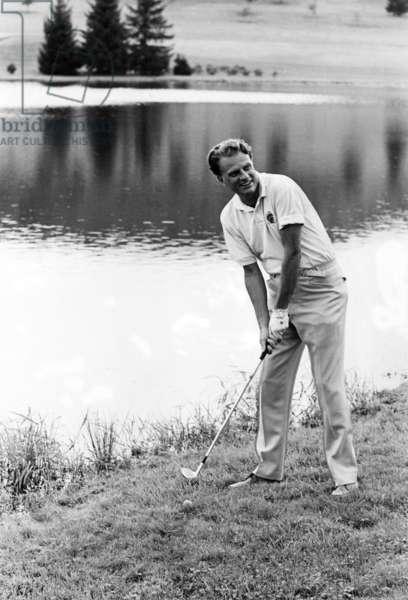 Evangelist Billy Graham playing golf. c. 1960s.