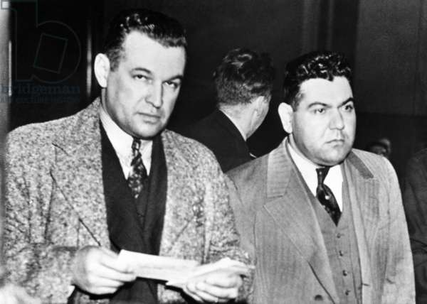 Joseph Accurso (right) of Cleveland in court in Brooklyn. He is known as the 'Al Capone of Cleveland', and was wanted in Akron for four murders since 1935. With Accurso is NYC Detective Joseph Kabelka. April 13, 1938
