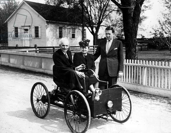 Henry Ford in his first automobile dated 1896. With him, wife Clara Bryant and grandson Henry Ford II, 1946