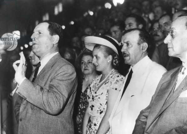Argentine President Juan Domingo Peron addressing an assembly in Buenos Aires. Behind him (in straw hat), is his wife, Senora Maria Eva Duarte de Peron. c. 1946-1950.