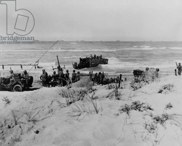 First U.S. troops ashore near Scoglitti, Sicily, during the Allied invasion of Sicily. They set up anti-aircraft guns to fend off Axis counter-attacks. Just behind them, another squad of invaders hits the beach. July 11, 1943, World War 2