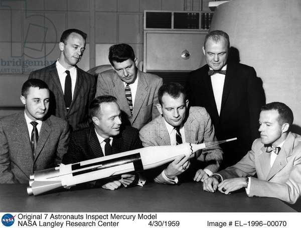 Project Mercury astronauts inspect Mercury model after they were introduced to the American public in April 1959. From left, front row: Gus Grissom. Scott Carpenter, Deke Slayton and Gordon Cooper; back row: Alan Shepard, Walter Schirra and John Glenn