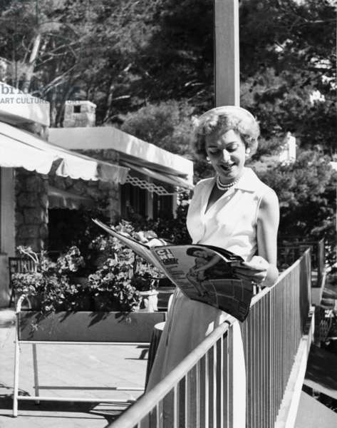 Christine Jorgensen, leafing through a film magazine on Capri, Italy, Sept. 22, 1954. She told reporters, two years after her public debut, she still hoped to become a night club entertainer.