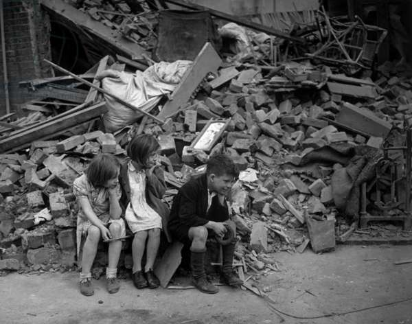 World War 2, Battle of Britain. Homeless children sit outside the wreckage of their home in London's East End, Sept. 1940