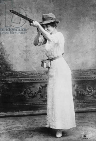 Woman posed with shotgun for trapshooting in 1914. In the 19th century trap shooters used the abundant Passenger Pigeon as their targets, until it became extinct from human overkill. Trap shooters switched to fake birds, 'clay pigeons' for their sport