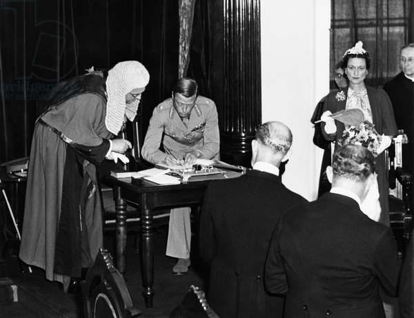 World War II. Prince Edward, Duke of Windsor, signing Oath of Allegiance to King George VI as he takes over duties as Governor General of the Bahamas. Right: Duchess of Windsor Wallis Simpson. August, 1940