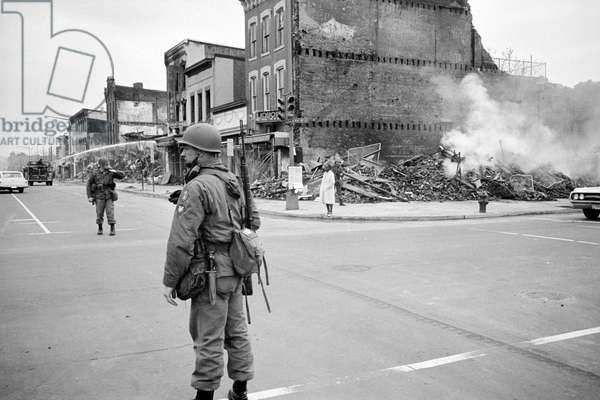D.C. Riot, April '68. aftermath, soldier standing guard in a Washington D.C. street with the ruins of buildings that were destroyed during the riots that followed the assassination of Martin Luther King Jr., by Warren K. Leffler, April 8, 1968