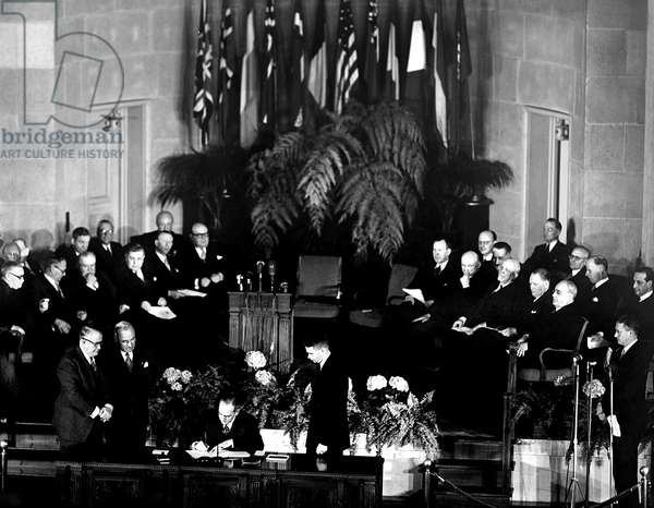 NATO, President Truman and V.P. Barkley, look on as Secretary of the State Dean Acheson signs the North Atlantic Treaty signing ceremony in Washington D.C., John W. Foley, State Dept. Treaty advisor, is on the platform, April, 1949