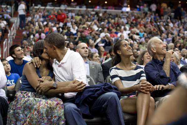 President Barack Obama kisses First Lady Michelle Obama for the 'Kiss Cam'. Malia and Joe Biden watch the kiss on Jumbotron screens the Verizon Center in Washington, D.C. July 16, 2012. They were attending the U.S. Men's Olympic basketball team's game against Brazil