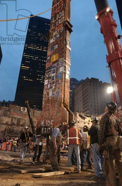 Construction workers maneuver the last piece of debris removed from Ground Zero. May 28, 2002. It was the 30-foot 'Column Number 1001B' of Two World Trade Center (South Tower). The steel beam, one of 47 that held up the South Tower, was plastered with mass cards, rosary beads, flags, photos of missing innocents, and letters from children to parents who would never be coming home. It is in the National Sept. 11 Memorial & Museum. U.S. Navy Photo by Bob Houlihan