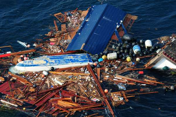 An overturned tug boat floats in the debris in left by the March 11 2011 tsunami Ofunato Japan. March 15 2011.,