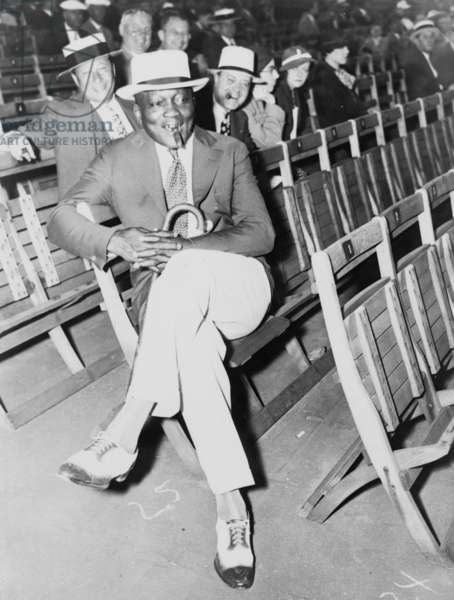 Jack Johnson (1878-1946) smoking a cigar and a holding cane while watching Baer-Carnera fight in Madison Square Garden in 1934