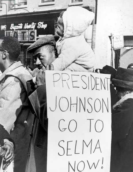 """Civil Rights, """"President Johnson go to Selma now!"""". African American man carrying a child on his shoulders with a placard telling President Johnson to go to Selma, Alabama. Photo by Stanley Wolfson, 1965"""