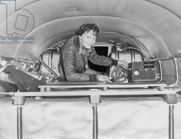 Amelia Earhart (1897-1937), checking equipment on her airplane. c. 1937