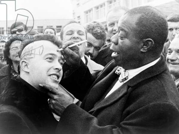 Louis Armstrong (1901-1971), African American Jazz musician, drawing a trumpet and autographing the side of a young man's head in Nice, France. 1960