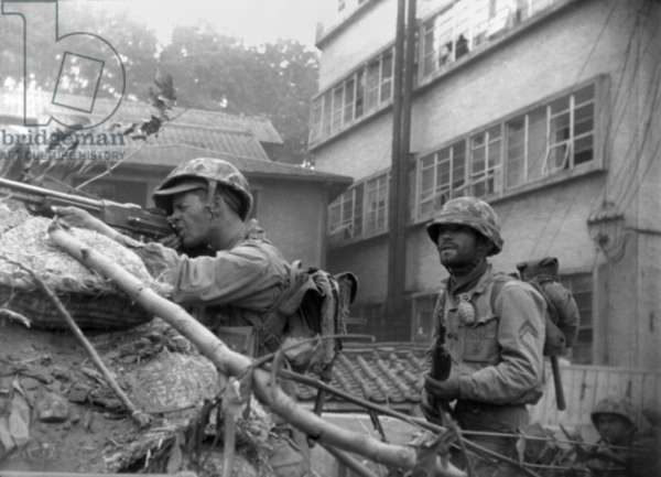 U.S. soldiers fire from behind a barricade at Communist-led North Korean forces in the streets of Seoul, Korea. 2nd Battle of Seoul. Sept. 22-28, 1950. Korean War, 1950-53
