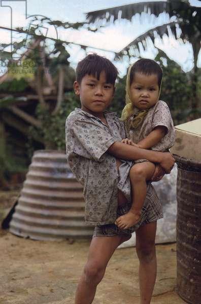 Vietnam War, Camp Campbell, Phu Bai, Republic of Vietnam. A Vietnamese boy carries a young child, c.late 1960s