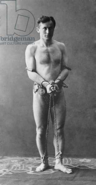 Harry Houdini (1874-1926), in chains. c. 1900