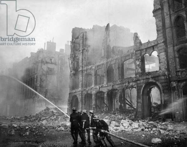 Fire fighting during World War 2 Battle of Britain. Firemen at work in bomb-damaged street in London, after Saturday night raid, c. 1941