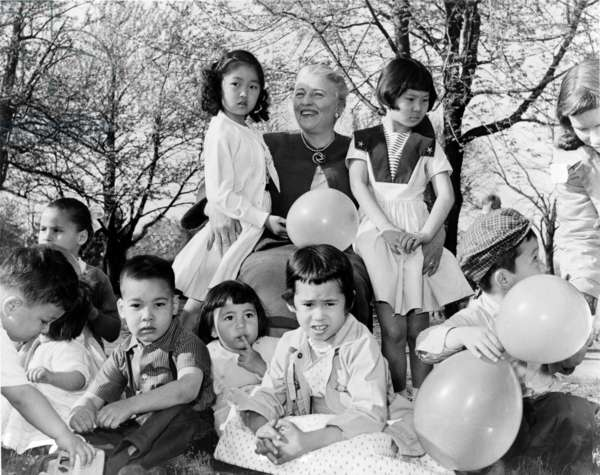 Pearl S. Buck (1892-1973), sits outdoors with group of Chinese-American children placed with families through her Welcome House adoption agency. Buck received Nobel Prize for Literature in 1938