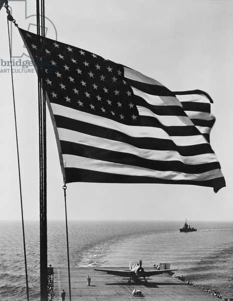 Flag of the United States snaps in the breeze over the USS Santee. November 1942. USS Santee was one of 4 escort carriers in Operation Torch, the Nov. 1942 Allied invasion of North Afric. Photo by Horace Bristol, member of the U.S. Naval Aviation Photographic Unit, under the command of Capt. Edward Steichen. World War 2